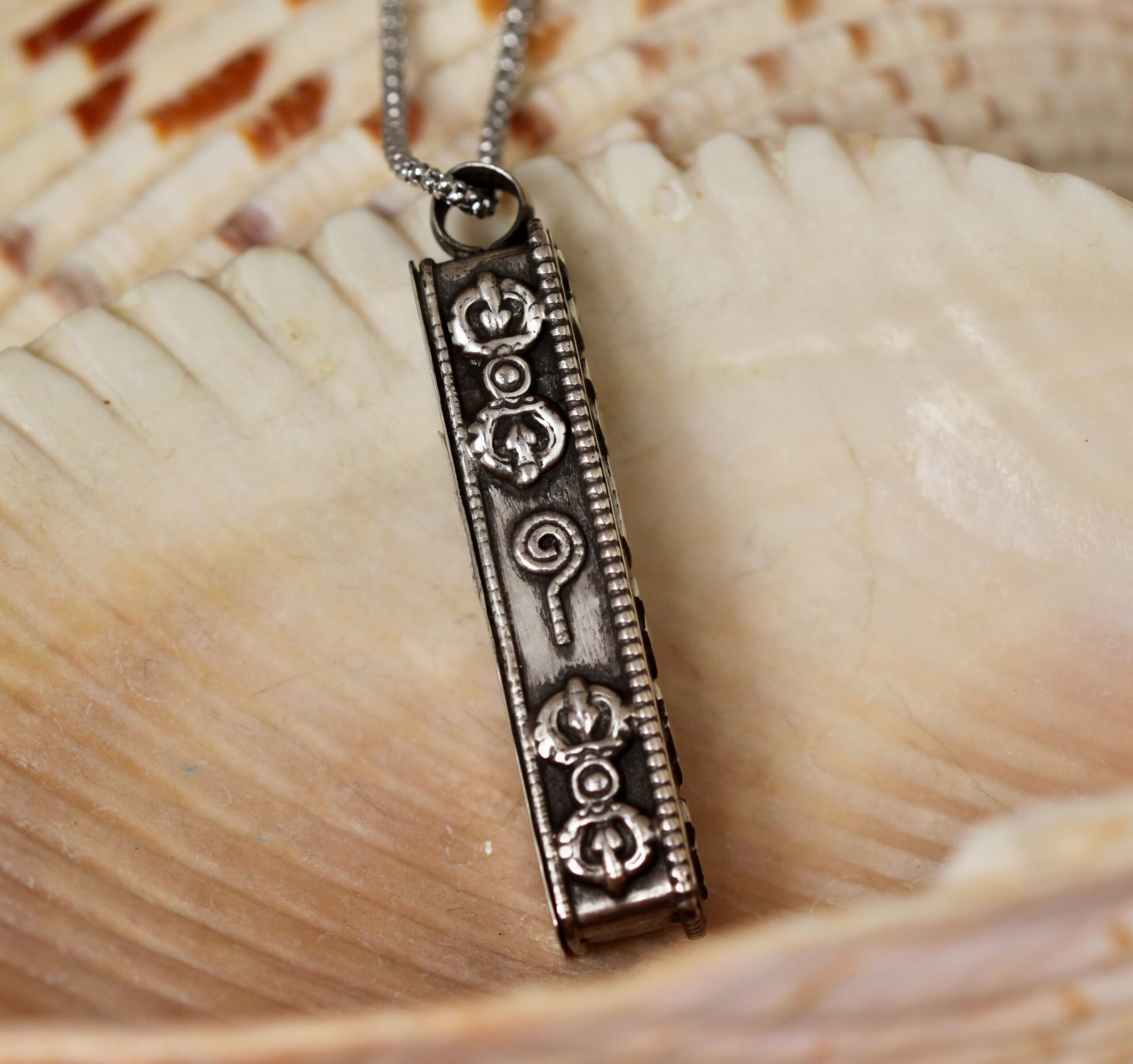 Side view of silver om mane padme hum prayer box necklace